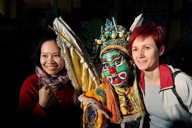 Khách thích thú chụp ảnh lưu niệm với nghệ sĩ biểu diễn nghệ thuật truyền thống trên đường phố. Ảnh: Văn Thành Châu
